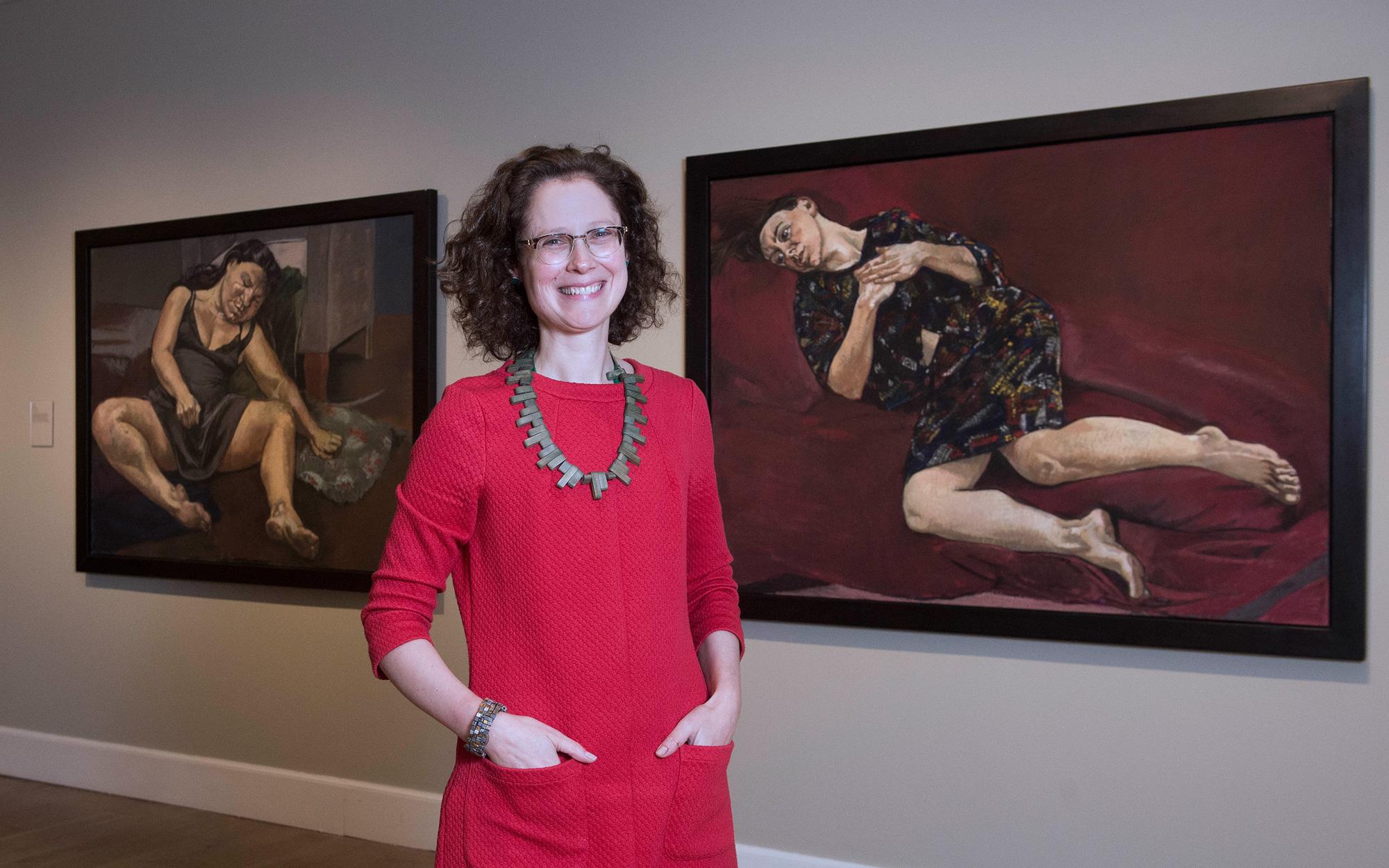 Curator Alice Strang standing alongside artworks by Paula Rego