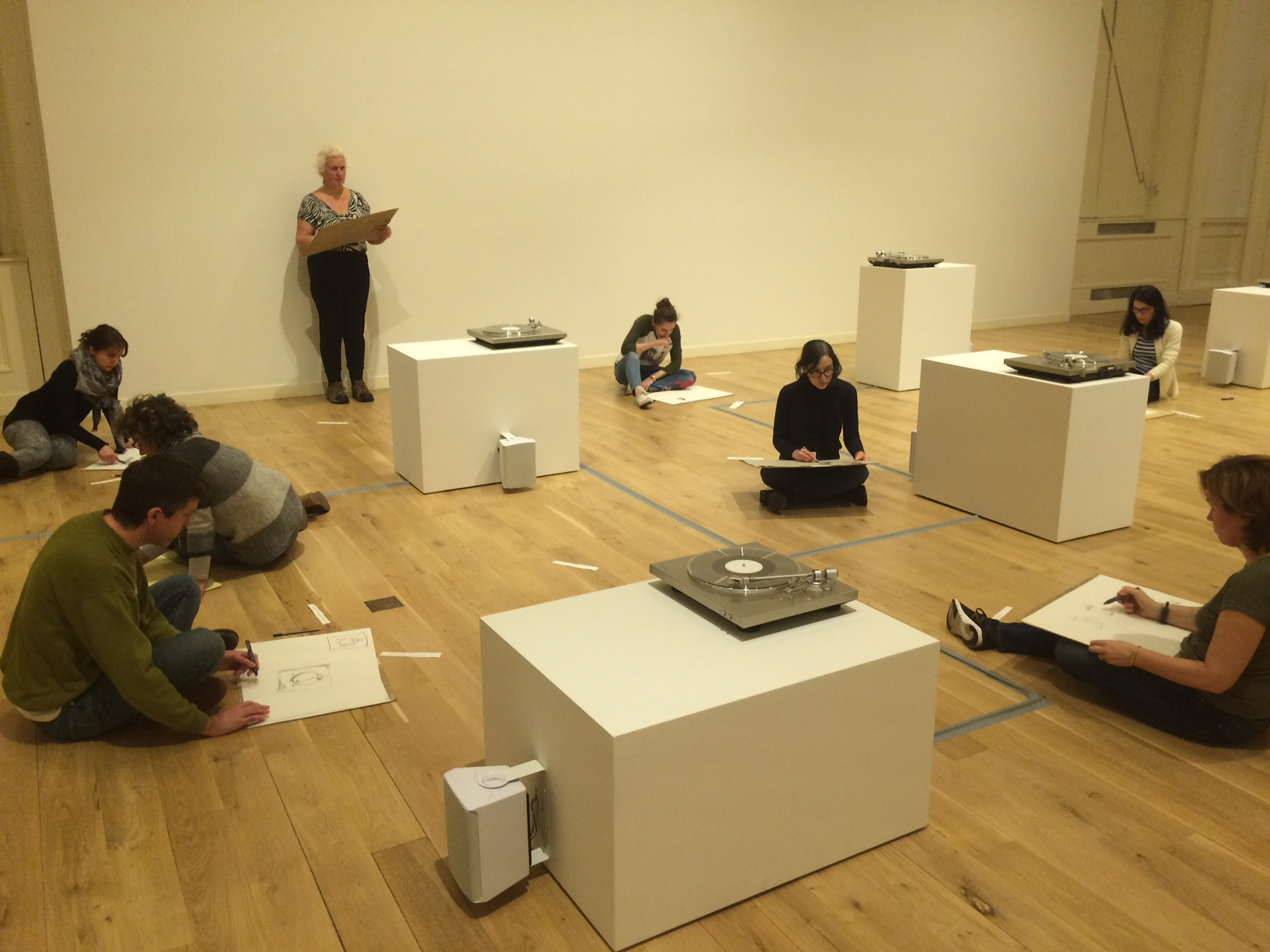 Various people sketching while sitting on the floor in the Gallery of Modern Art surrounded by turntables on plinths