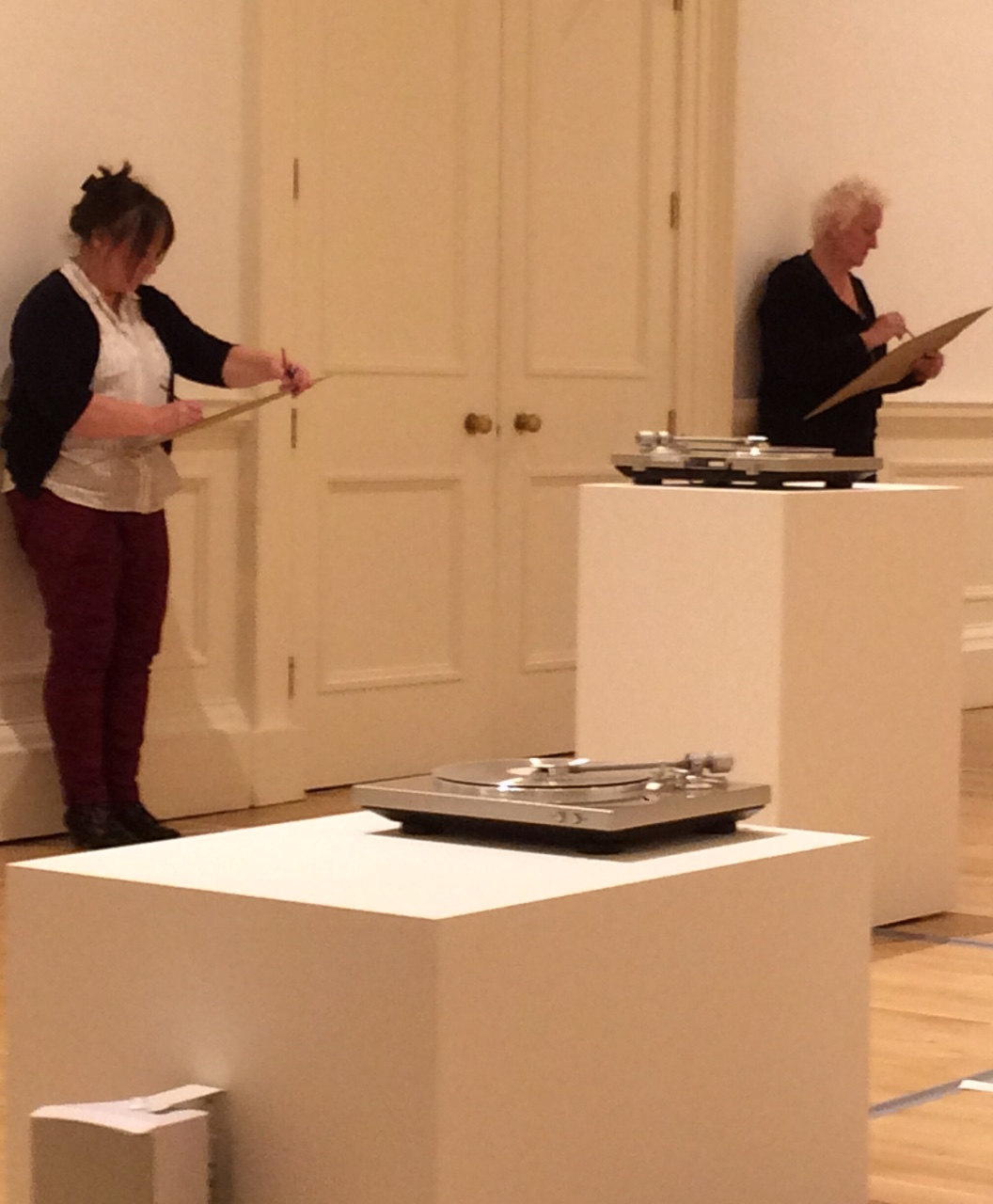 Two people sketching in the Gallery of Modern Art surrounded by turntables on plinths