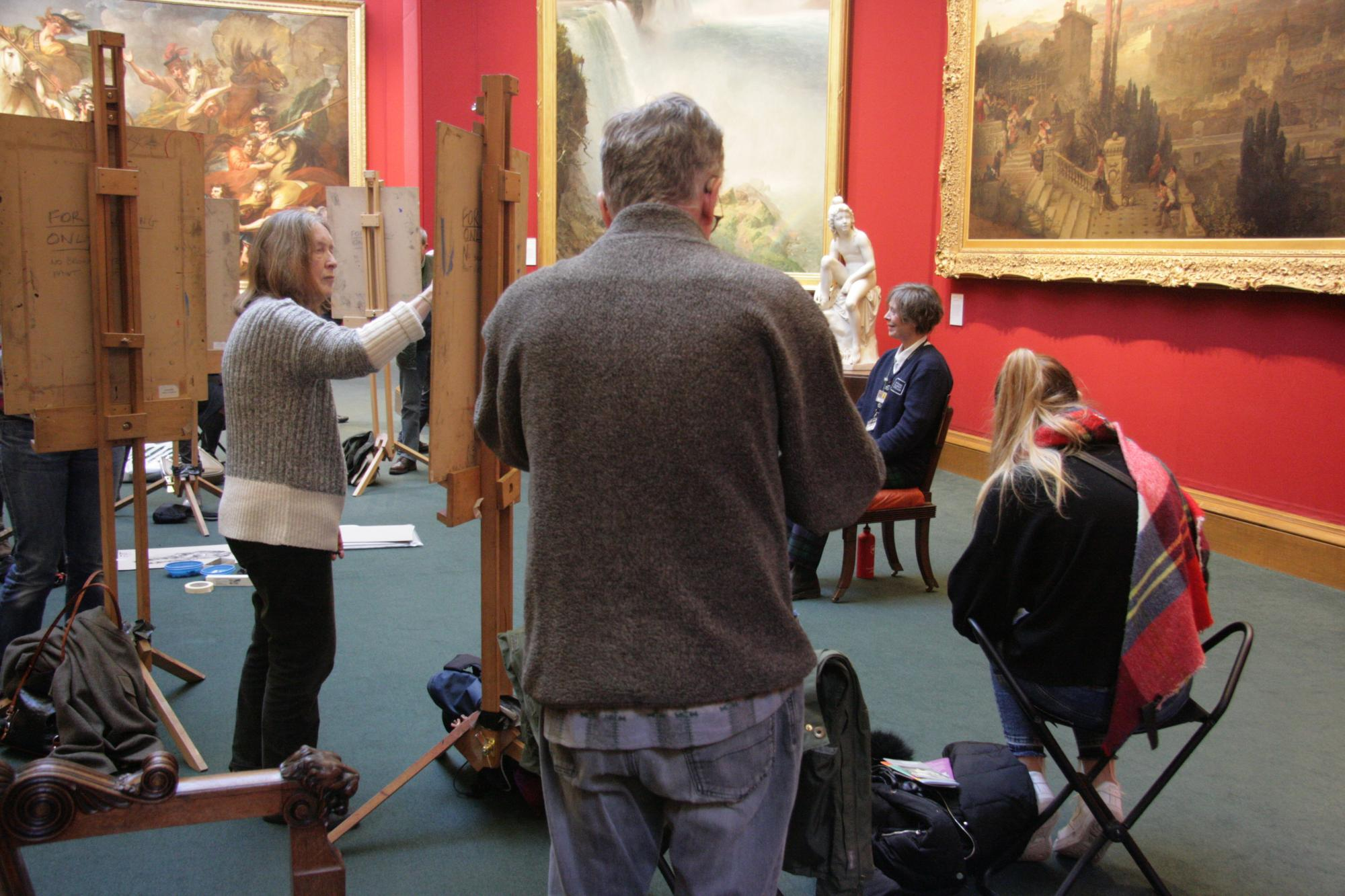 A group of people standing at easels while sketching a seated figure in the Scottish National Gallery