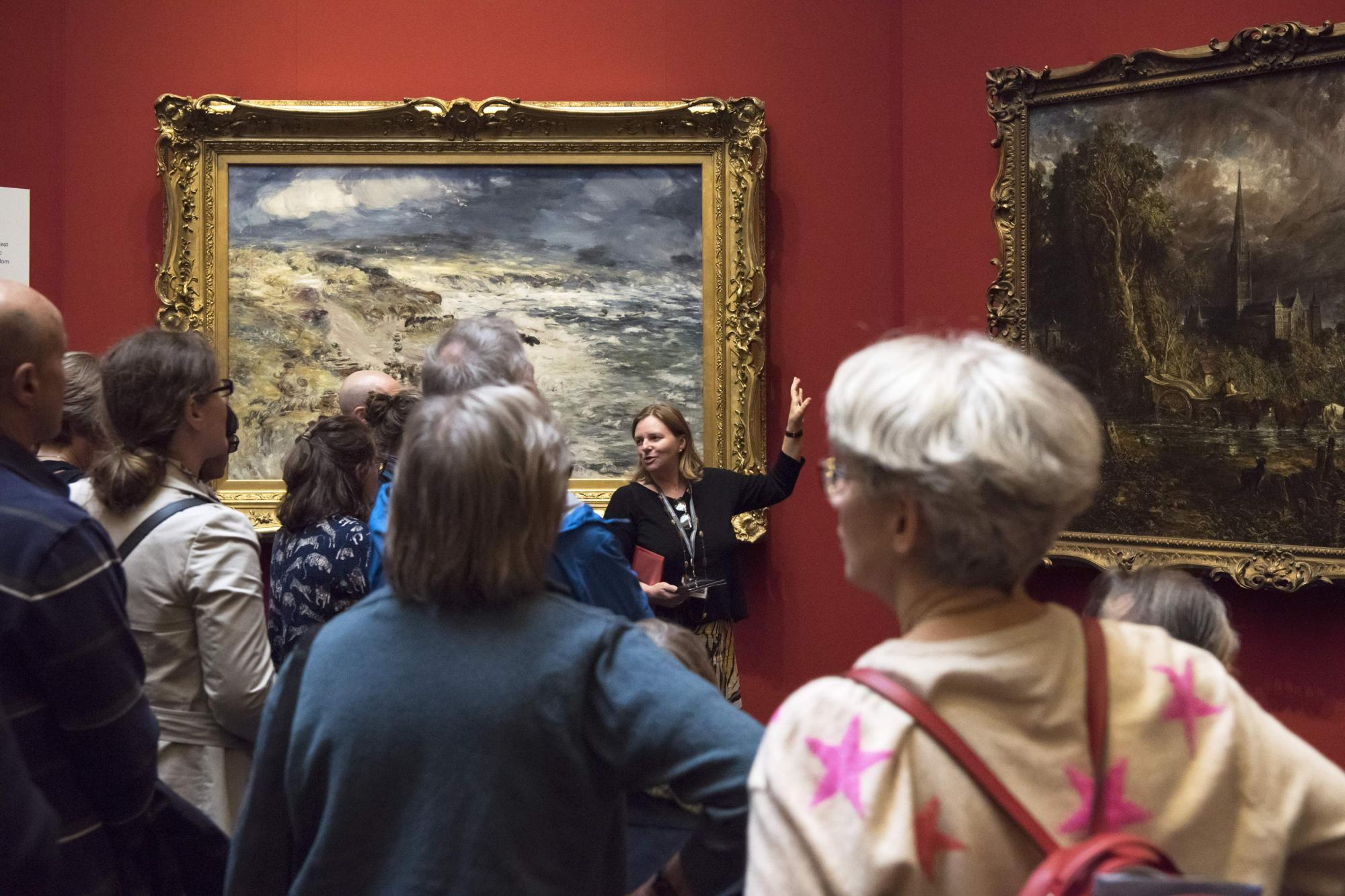 Visitors gathered around a tour guide who stands in front of paintings by Constable and McTaggert