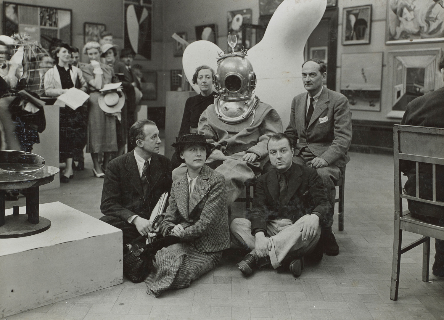 Photograph of Salvador Dali in a deep sea diving suit seated in a group with other Surrealists at the 1936 International Surrelist Exhibitio