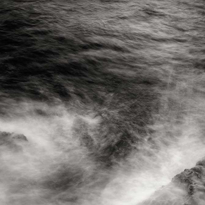 Close up photograph of swirling waves with the motion of the waves captured as a blur in some instances.