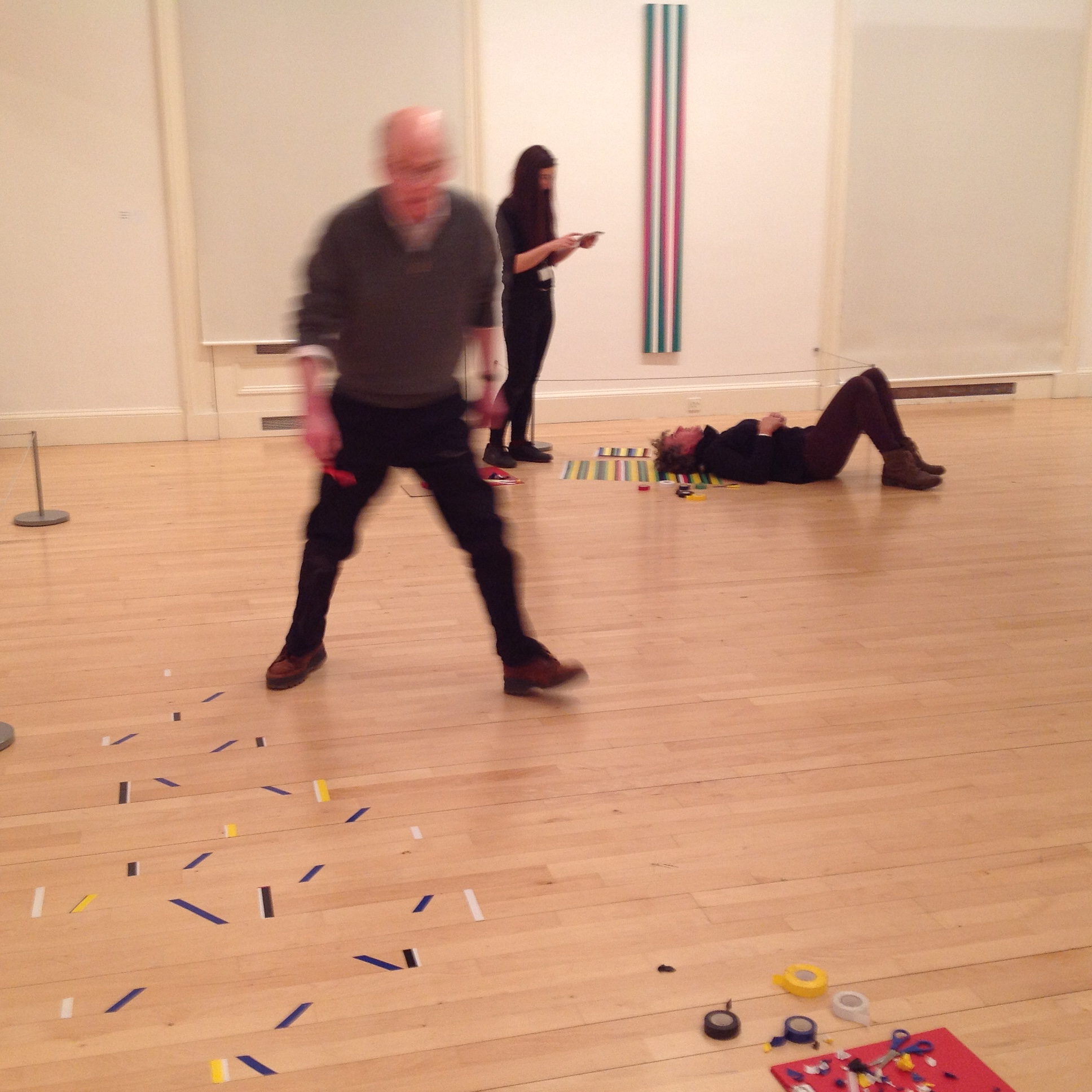 Various people in the Gallery of Modern Art using tape, scissors, paper and their own bodies to create artworks