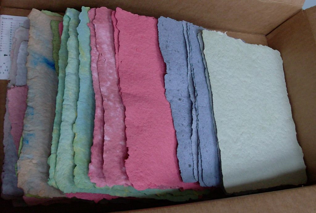 Various sheets of coloured paper in a box