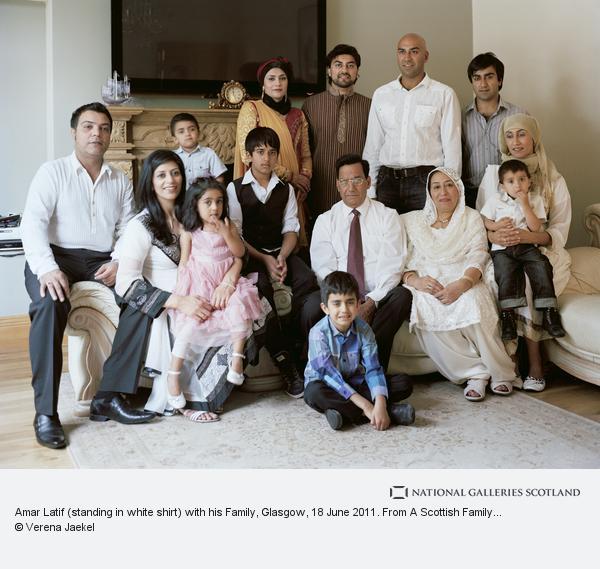 Amar latif standing in white shirt with his family glasgow 18 june 2011 from a scottish family portrait series