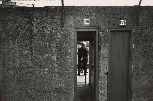 Football Ground, Policeman and Man observed through Turnstile Gate