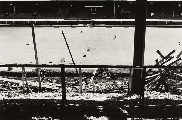 Football Ground with Broken Stand in Foreground, Water Sprinklers on Turf