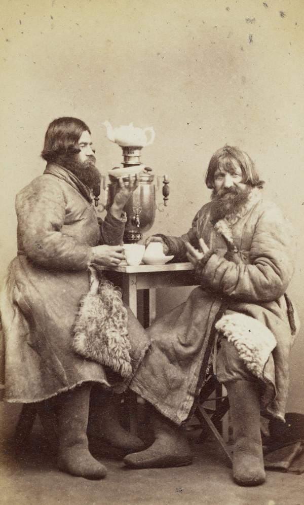 Two men drinking tea, with samovar