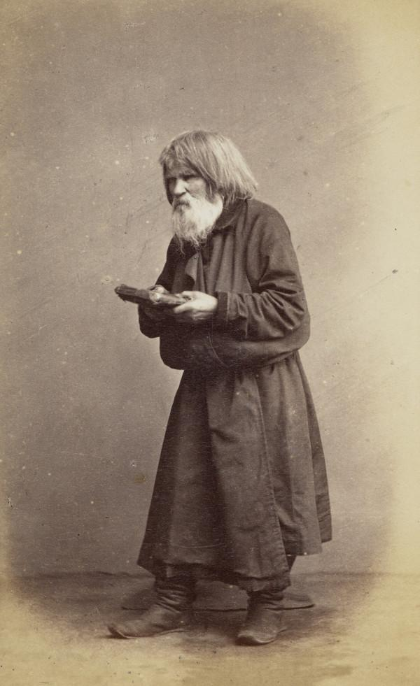 An 'old believer' - religious mendicant of St Petersburg - old bearded man with book held out in front of him