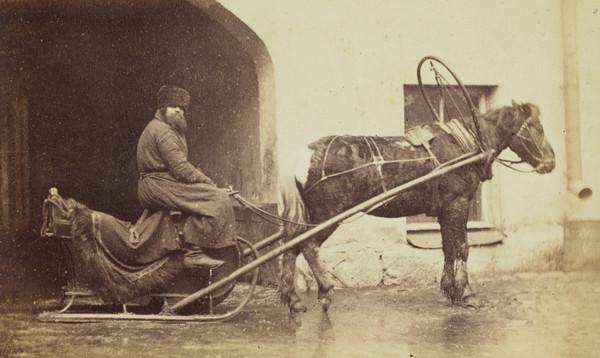 Horse and sledge and coach driver in winter. Taken out of doors