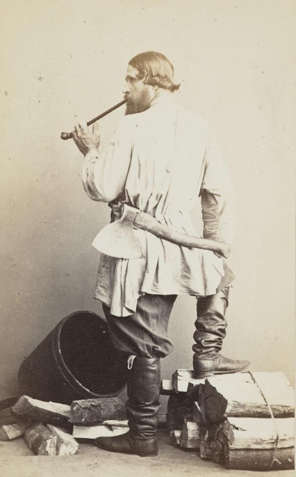 Woodcutter, standing with back to camera, seen in profile smoking a longstemmed pipe