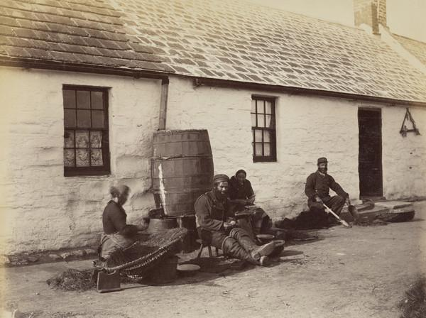 'West Haven Carnoustie 1880'. Two fisherwomen and a man baiting lines outside cottage, second man seated with spade and shovel, presumably for... (1880)