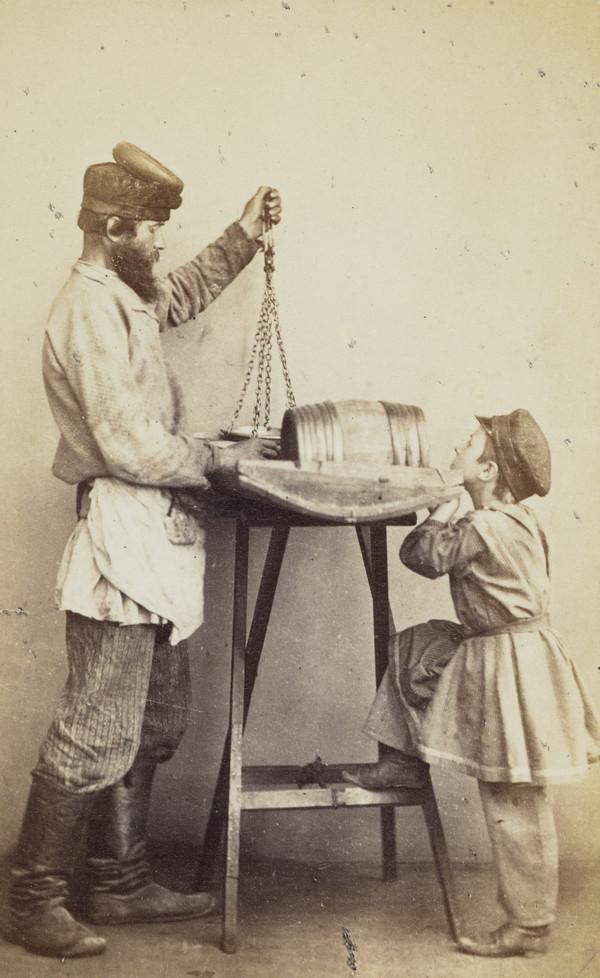 Man with scales, folding table with a band on it, watched by a child. The man has a hat with a pad on it, probably for carrying goods on his head...