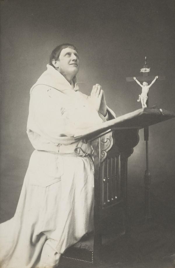 Unknown man dressed as monk, praying