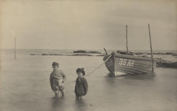 'West Haven'. Two children wading in the sea, boat in the background