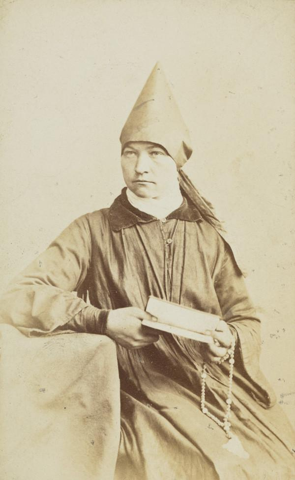 An 'old believer' - half-length, female religious with pointed hat, and holding prayer book and beads