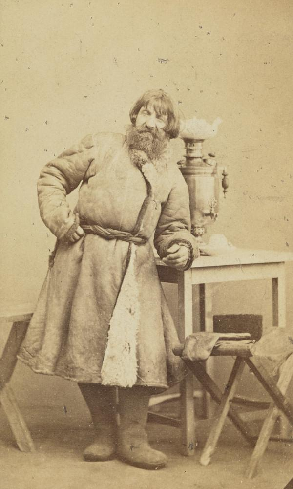 A tea-drinker, peasant in sheepskin coat and felt boots leaning on a table upon which is a samovar, teapot and upturned teacup