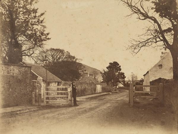 Street with unidentified man leaning against gate