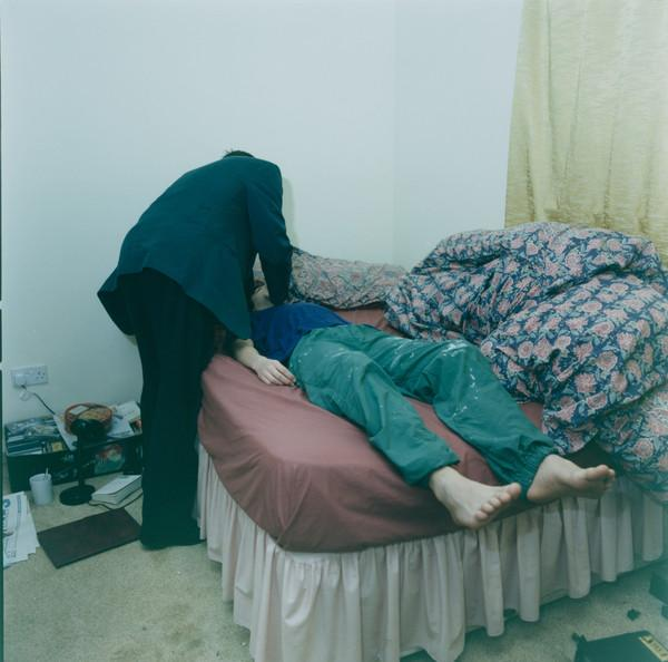 Untitled (Doctor Examining a Man Lying on a Bed)