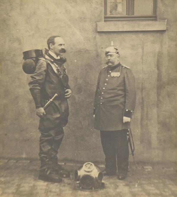 Dr John Scott Haldane, 1860 – 1936. Physiologist. Wearing a diving suit in the company of a German soldier