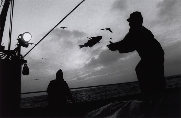 Stuart Kerr and Raymond Peat cleaning the decks at dusk, aboard the 'Mairead', North Sea (1993)