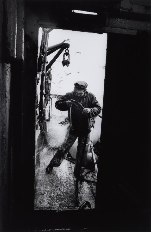 Raymond Peat washes his oilskins after gutting fish, aboard the 'Mairead', North Sea (1993)