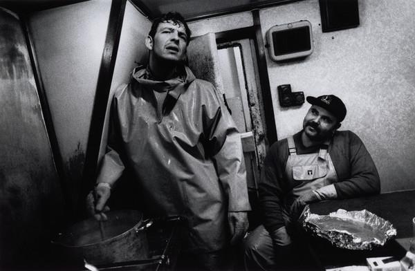 Stuart Kerr prepares dinner for the crew, whilst Andrew Gay looks on, aboard the 'Mairead', North Sea (1993)
