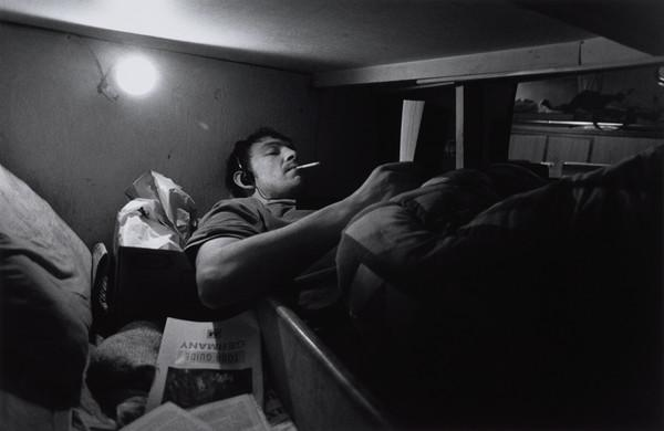 Stuart Kerr relaxes in his bunk at the end of the day, aboard the 'Mairead', North Sea (1993)