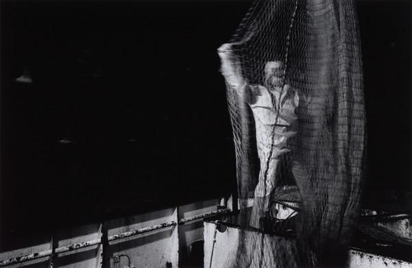 Tam Gay checks the nets for holes aboard the 'Mairead', a seine net trawler, North Sea (1993)