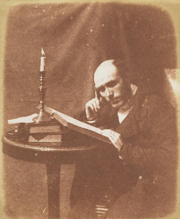 Unidentified man, reading by candlelight
