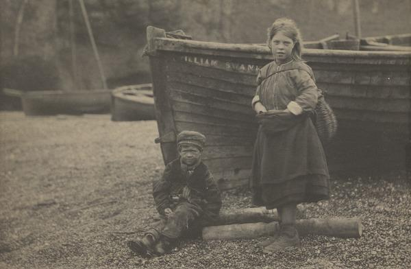 'At Auchmithie 1881'. Boy and girl on shore by boat, identified as 'William Swank(ie?)' (1881)