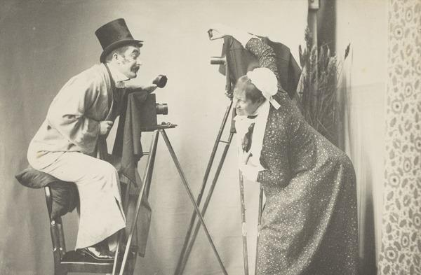 Comic photography scene of a man and a man dressed as a woman taking each other (1887)