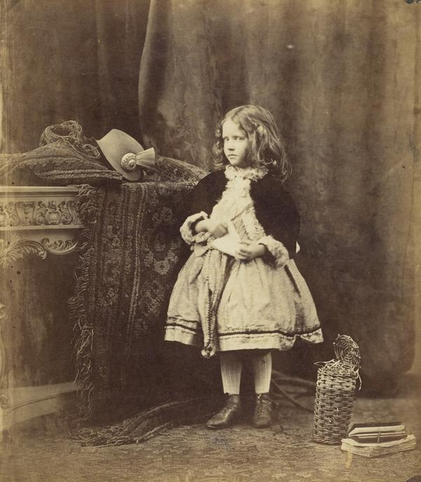 Unknown young girl, standing by a table, basket and books at her feet (About 1860)