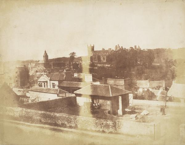 Linlithgow from above the railway line, shed and station in foreground.  Town Hall, St Michael's Church and Linlithgow Palace in the background ... (1843 - 1847)